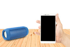 Man Hand holding smart phones and portable speaker on wooden table. Hand holding smart phones and portable speaker on wooden table Stock Photo
