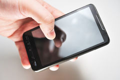 Hand holding a smartphone. Smartphone with transparent lcd screen against grey background Royalty Free Stock Images