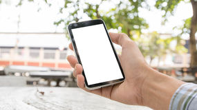 Hand holding smartphone against on smooth background. Royalty Free Stock Image