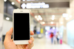Hand holding smartphone with airport passenger background Stock Images