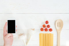 Hand holding smartphone with blank screen and fresh raw tomatoes with pasta on wooden table. Top view of hand holding smartphone with blank screen and fresh raw Stock Images