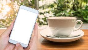 Hand holding smartphone with blank screen mobile and coffee cup Stock Images