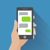Hand holding smartphone with blank speech bubbles Stock Photography