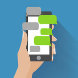 Hand holding smartphone with blank speech bubbles Stock Photos
