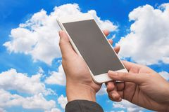 Hand holding smartphone on blue sky. Background Royalty Free Stock Photo