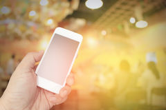 Hand holding the smartphone on blur restaurant background Royalty Free Stock Image