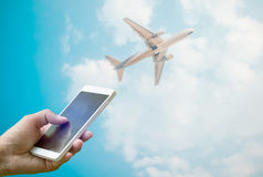 Hand holding smartphone on blurred flying airplane in clear sky royalty free stock photography