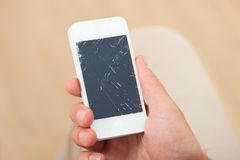 Hand holding smartphone with broken screen. Cropped image of man's hand holding smartphone with broken screen at home stock photo