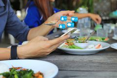 Hand holding smartphone for checking social media with icon or hologram in restaurant, Communication network internet and Business royalty free stock photography