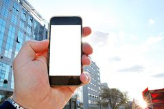 Hand holding smartphone. City in the background Royalty Free Stock Photos