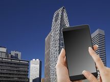 Hand holding smartphone. City in the background. Women smartphone mobile phone with a scene of travel stock images