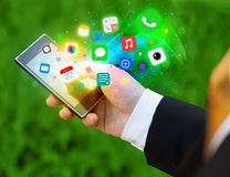 Hand holding smartphone with colorful app icons Stock Images
