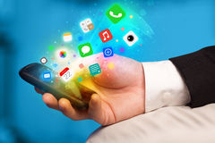 Hand holding smartphone with colorful app icons Stock Photos