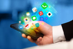 Hand holding smartphone with colorful app icons Stock Photo