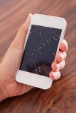 Hand holding smartphone with cracked screen Royalty Free Stock Photography