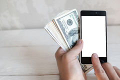 Hand holding smartphone and dollars, mockup Royalty Free Stock Image