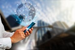 Hand holding smartphone with globe and digital connections on blurred city background Stock Image