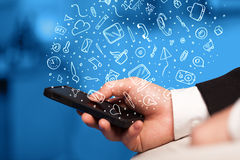 Hand holding smartphone with hand drawn media icons and symbols Stock Image
