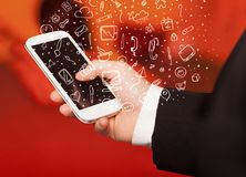 Hand holding smartphone with hand drawn media icons and symbols Stock Photo