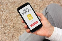 Hand holding smartphone with we are hiring apply now concept on. Screen. All screen content is designed by me Royalty Free Stock Photos