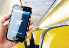 Hand holding smartphone inside the plane Stock Image