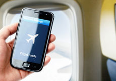 Hand holding smartphone inside the plane Stock Photo