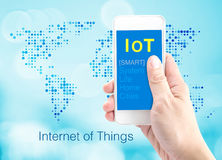 Hand holding smartphone with Internet of things (IoT) word at do Royalty Free Stock Images