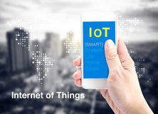 Hand holding smartphone with Internet of things (IoT) word with Stock Image