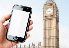 Hand holding smartphone in London city Royalty Free Stock Photos