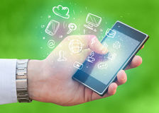 Hand holding smartphone with media icons Stock Photography