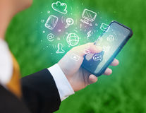 Hand holding smartphone with media icons Royalty Free Stock Image