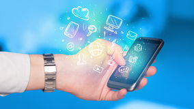 Hand holding smartphone with media icons Royalty Free Stock Photography