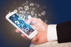 Hand holding smartphone with media icons and symbol Royalty Free Stock Photo
