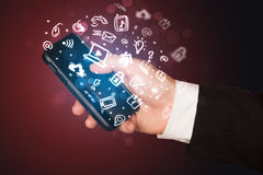 Hand holding smartphone with media icons and symbol Stock Photo