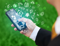 Hand holding smartphone with media icons and symbol Royalty Free Stock Photography
