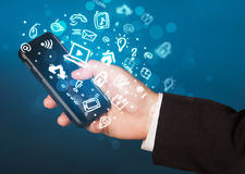 Hand holding smartphone with media icons and symbol Stock Image