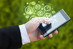 Hand holding smartphone with mobile app choices. Hand holding smartphone with glowing mobile app choices Stock Photos