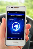 Hand holding smartphone with mobile payment. In the car Royalty Free Stock Photo