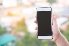 Hand holding smartphone or mobile phone with city building background and copy space. stock photo