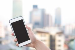 Hand holding smartphone or mobile phone with city building background and copy space. stock photos