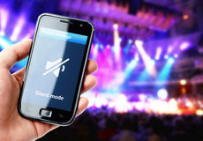 Hand holding smartphone with mute sound during concert Stock Photos