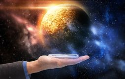 Hand holding smartphone over planet in space. Business, future technology and people concept - businessman hand holding smartphone over planet in space Stock Photography
