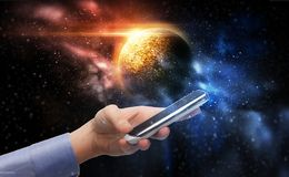 Hand holding smartphone over planet in space. Business, future technology and people concept - female hand holding smartphone over planet in space background Stock Photos