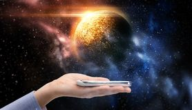 Hand holding smartphone over planet in space. Business, future technology and people concept - female hand holding smartphone over planet in space background Royalty Free Stock Photo