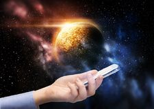 Hand holding smartphone over planet in space. Business, future technology and people concept - female hand holding smartphone over planet in space background Stock Images