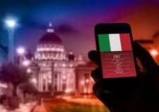 Hand holding smartphone with Rome St Peter Vatican city background. royalty free stock images