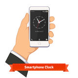Hand holding smartphone with round clock widget Royalty Free Stock Images
