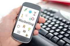Marketing concept on a smartphone. Hand holding a smartphone showing a marketing concept royalty free stock photography