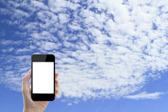 Hand holding smartphone on sky background Stock Photos