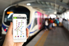 Hand holding smartphone with subway station map application Stock Photos